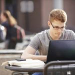 college Student studying with laptop and taking notes in distance learning