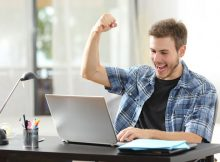 Distance learning college student triuphing with raised fists